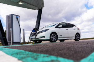 View from the ground looking up. White electric car charging point with Nissan Leaf connected. EV parking and recharging station.